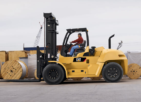 Sideview of an Operator Using a Cat IC Pneumatic Tire Diesel Forklift Outdoors