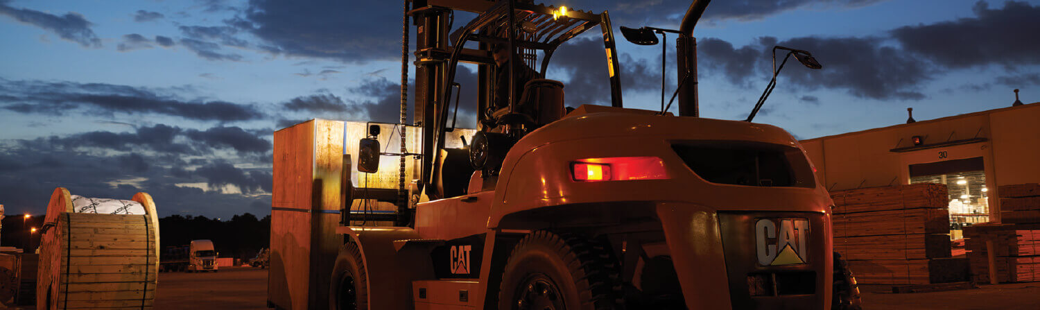 Large CAT Forklift Truck Working Outdoors at Night