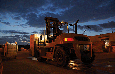 Class 5 CAT Forklift Moving Materials Outdoors at Night