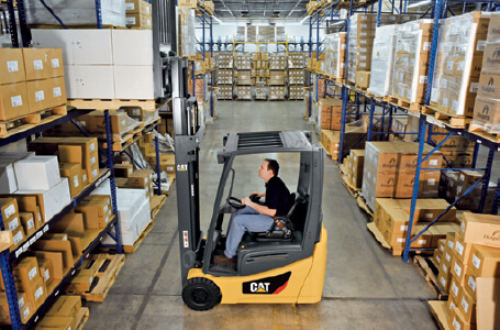 Worker lifting boxes off shelf with Cat forklift