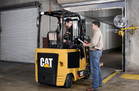 Worker with a clipboard talking with worker on Cat forklift