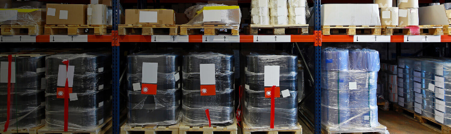 Barrels wrapped in plastic on warehouse shelves