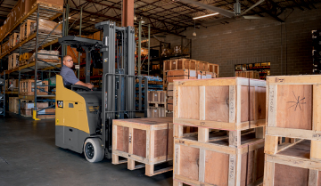 Pallets Being Stacked by a Cat Stand-Up Counterbalanced Lift Truck�