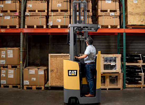 Operator Using a Cat Stand-Up Counterbalanced Forklift to Load Pallets onto Shelves