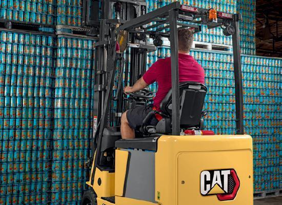 Rear view of worker picking up pallet with Cat small electric cushion forklift