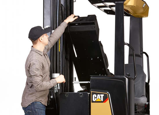 Worker lifting up seat of Cat moving-mast reach truck