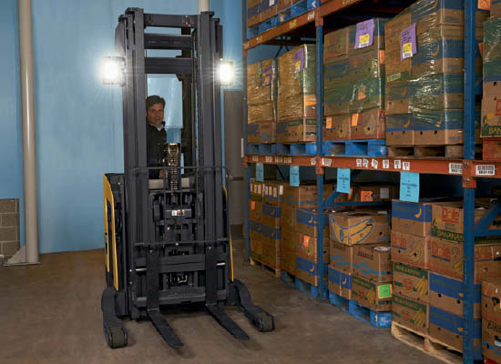 Operator in Cat pantograph reach truck positioned next to shelf of boxes