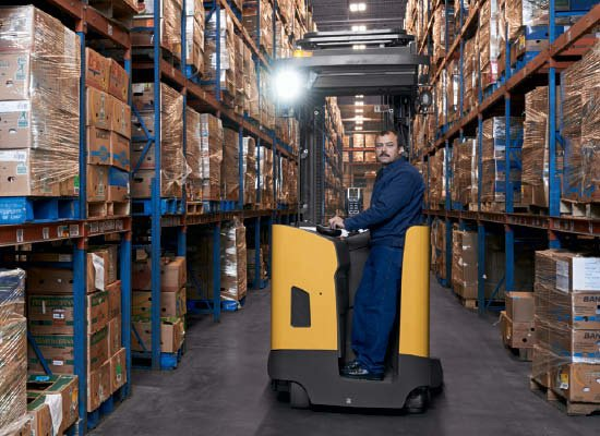 Side view of worker standing in Cat pantograph reach truck with light on