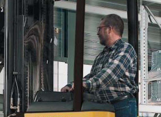 Close-up of worker operating the controls of Cat stand-on stacker