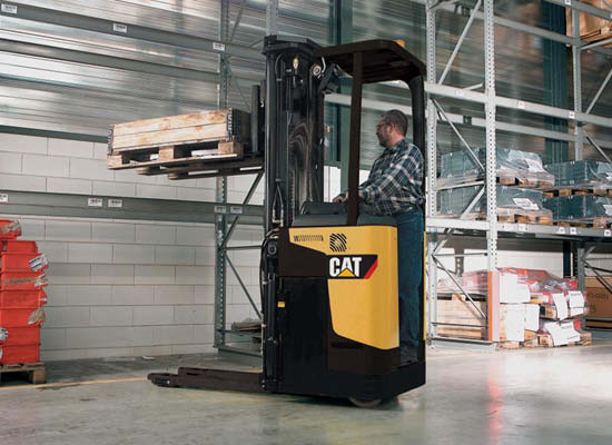 Worker moving pallets through narrow space with Cat stand-on stacker