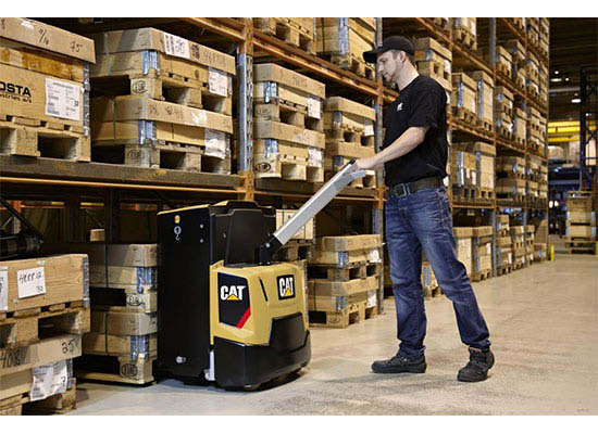 Worker picking up wooden pallets with Cat power pallet truck