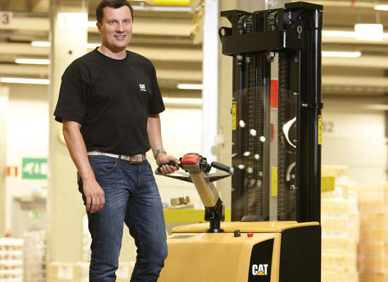 Smiling worker with one hand on the Cat pedestrian stacker lever