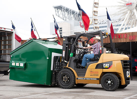 Man with Cowboy Hat Lifting a Recycling Bin with a CAT Forklift