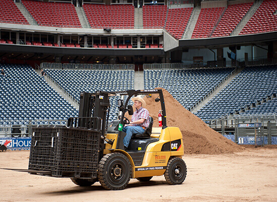 Operator Driving a Crate with a Cat Forklift Actross the Rodeo Stadium
