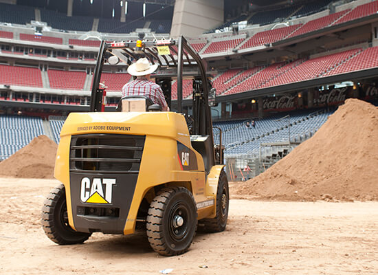 Man Driving a Cat Forklift in the Houston Rodeo Stadium