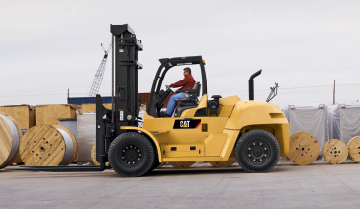Operator Carrying Loads Outside with a Large Cat IC Pneumatic Tire Diesel Forklift