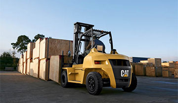Operator Using a Large Cat IC Pneumatic Tire Forklift to Stack Boxes Outdoors