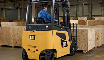 Worker lifting wooden crates with Cat pneumatic forklift