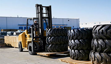 Cat diesel forklift next to stacks of large tires