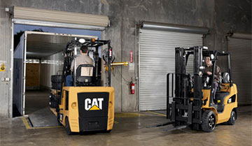 Two operators driving Cat forklifts into loading trucks