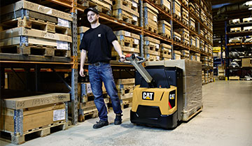 Worker pulling Cat power pallet truck with pallets on it