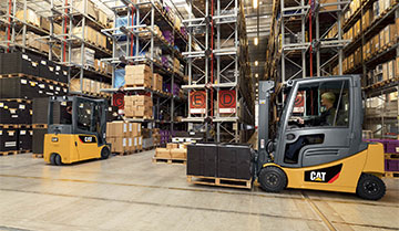 Cat pneumatic forklift moving materials in a warehouse while other forklift sits in background