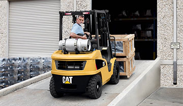 Man Reversing down a Warehouse Ramp on a Small IC Cat Lift Truck
