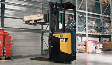 Brochure image of worker operating Cat stand-on stacker