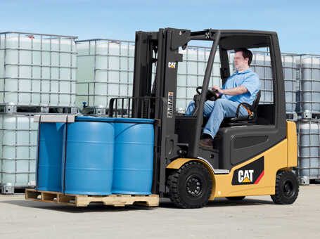 Worker moving blue barrels on pallet with Cat class i forklift