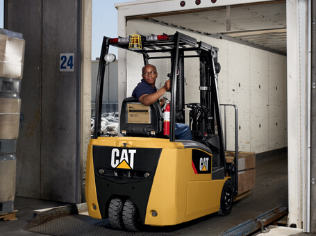 Worker backing Cat class i forklift out of moving truck