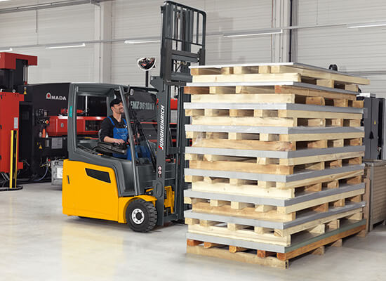 Worker getting ready to pick up stack of wooden pallets with Jungheinrich counterbalance truck