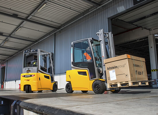Two Jungheinrich pneumatic tire lift trucks driving outside warehouse
