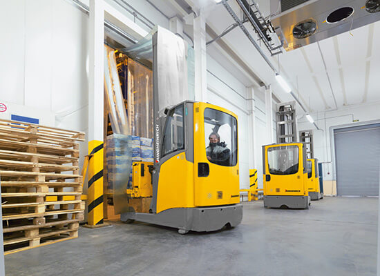 Jungheinrich Sit Down Moving Mast Reach Trucks in Use in a Warehouse