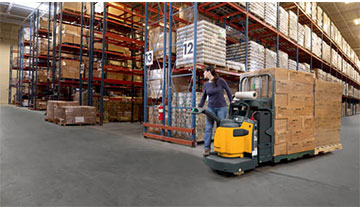 Woman Riding a Jungheinrich End-Rider Pallet Truck through a Warehouse