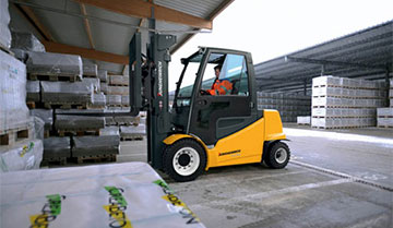 Operator Driving a EFG 535k-S50 Electric Pneumatic Lift Truck with Materials Outdoors