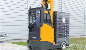 Worker driving Jungheinrich multi-purpose moving mast reach truck transporting materials in back