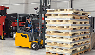 Side View of an Operator using a Jungheinrich Counterbalance Forklift to Pick Up Pallets