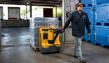 Worker pulling Jungheinrich walkie pallet truck loaded with bottles through warehouse