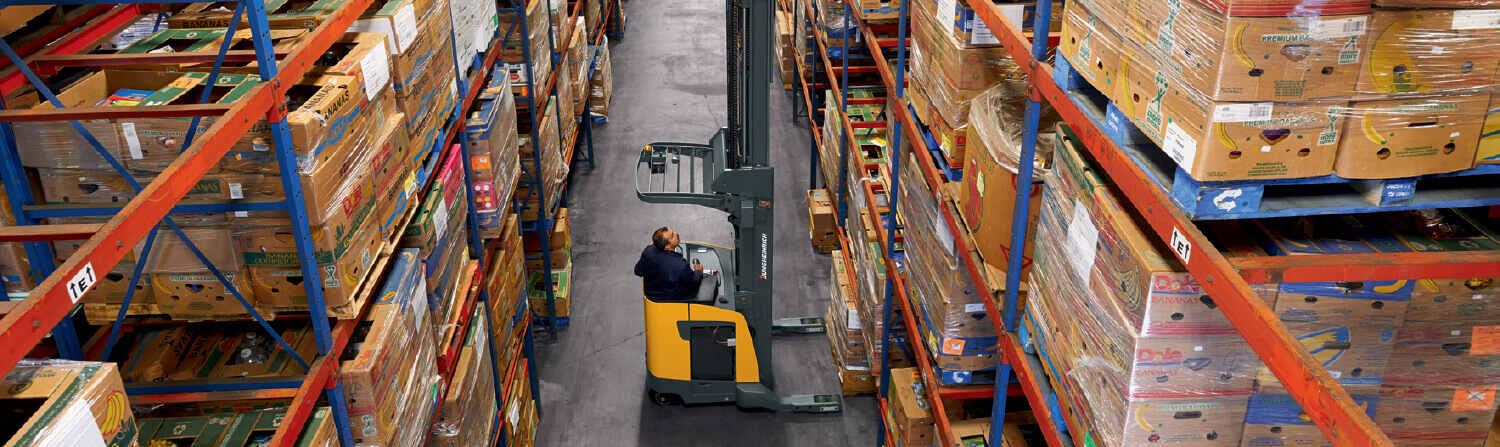 Worker using Jungheinrich order picker to reach high shelf
