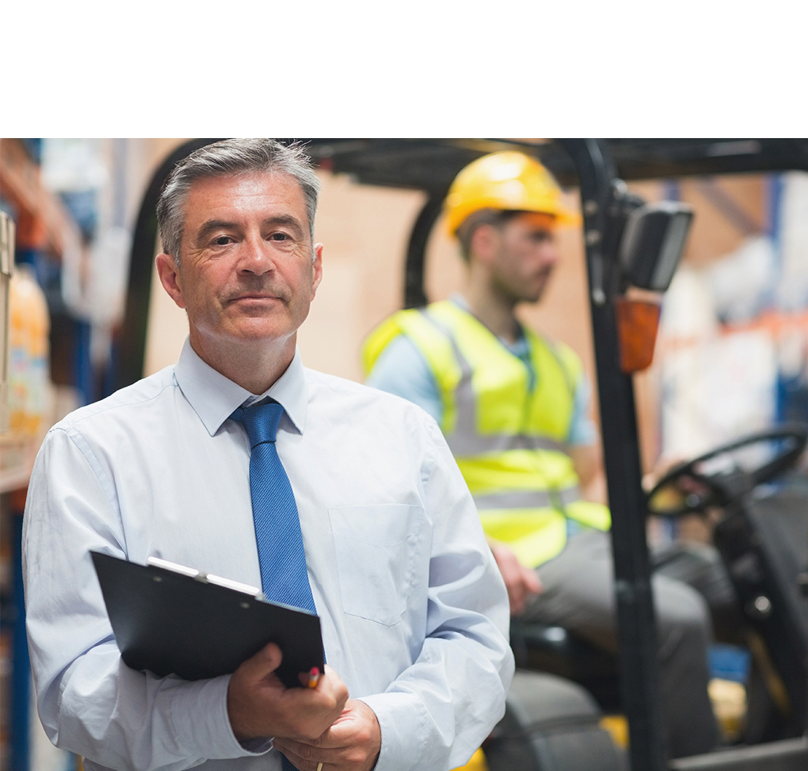 Man with a Clipboard Standing in Front of a Man in a Forklift