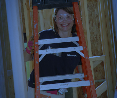 MCFA employee with safety glasses smiling behind ladder