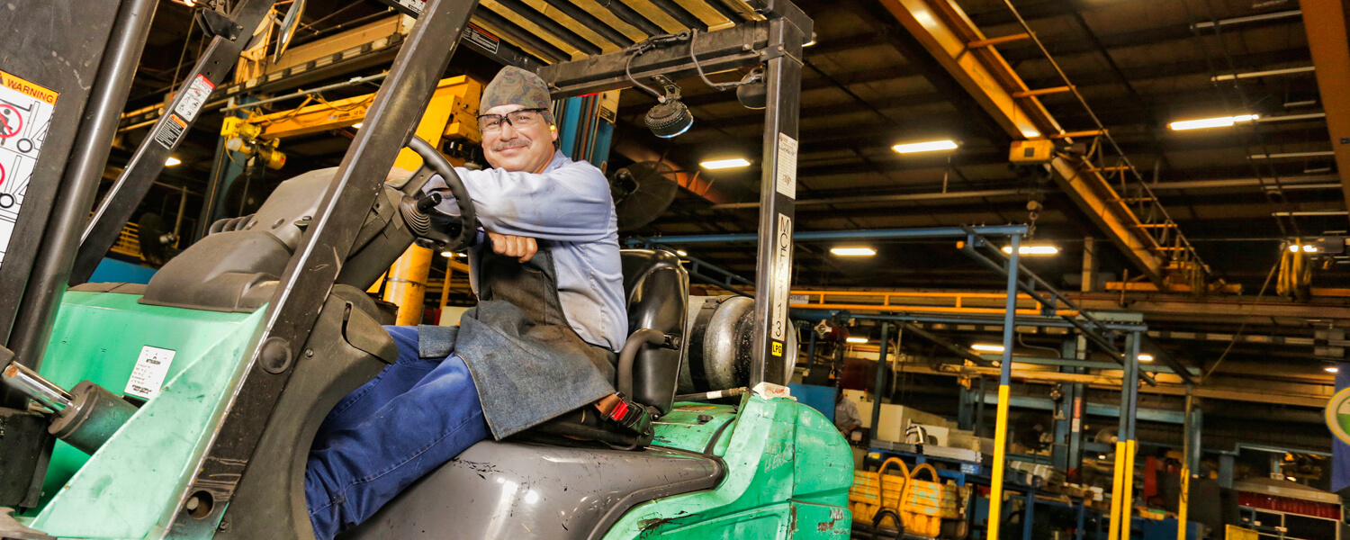Forklift operator with safety glasses sitting in compartment and smiling