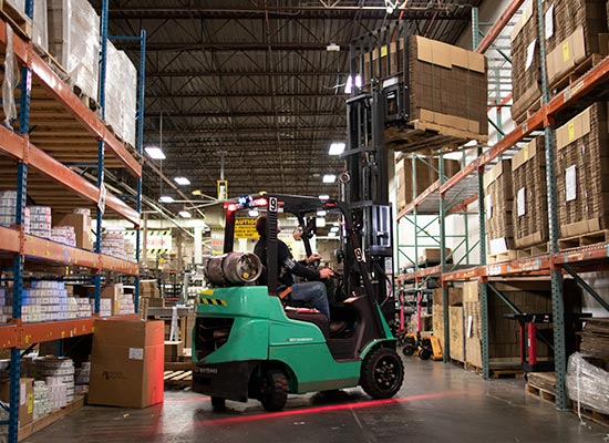 Mitsubishi Forklift Working Between Aisles in a Rimports Warehouse