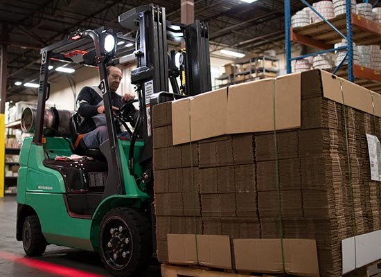 Operator Lifting up Merchandise on a Pallet with a Mitsubishi Forklift