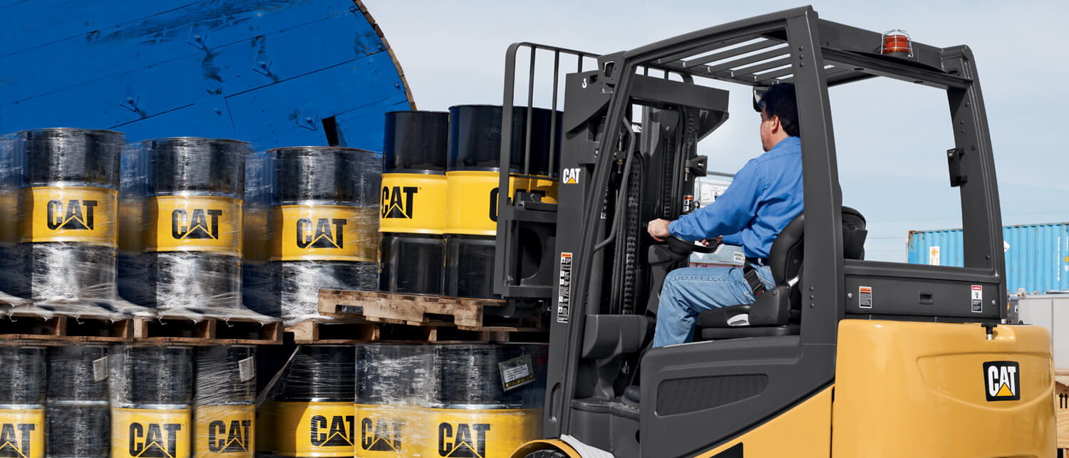 Worker lifting Cat brand barrels with Cat forklift