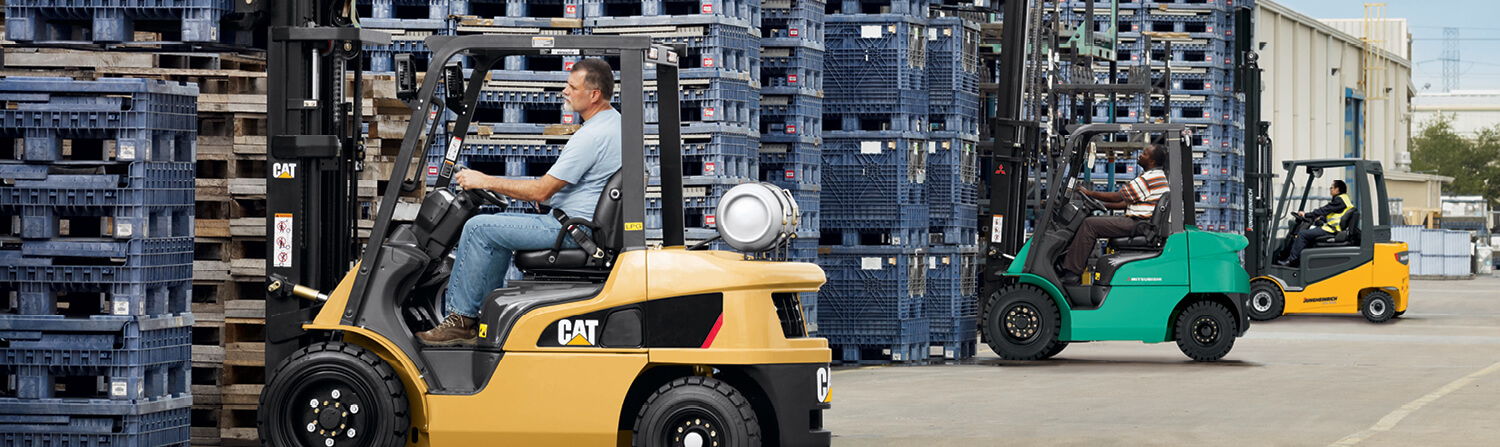 Cat, Mitsubishi and Jungheinrich forklifts lined up lifting crates