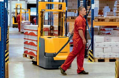 Man pulling forklift by handle through warehouse