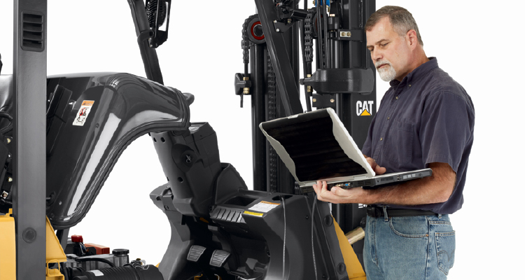 Man looking at laptop connected to forklift