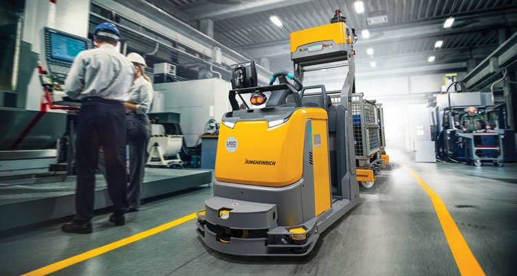 automated tugger forklift in warehouse with people