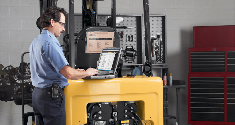 Man on laptop checking forklift